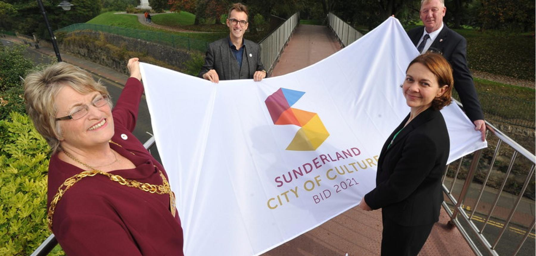 Picture of members of the cultural partnership with the city of culture flag.